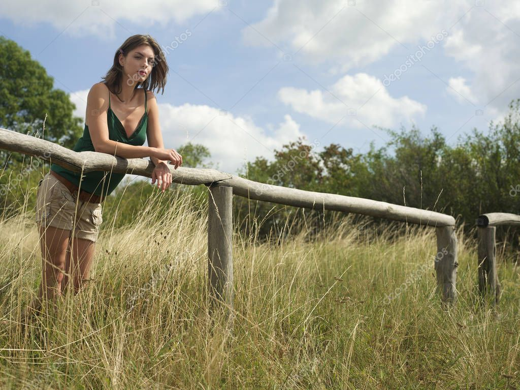 woman leaning on wooden fence