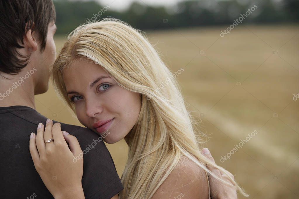 Young woman leaning on young man's arm