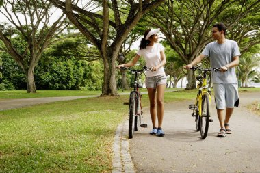 Couple in park, holding bicycles