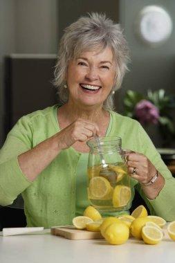 Mature woman holding lemon aid