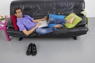 Man on sofa using laptop