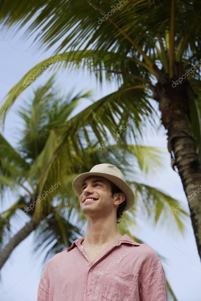 man standing under palm tree