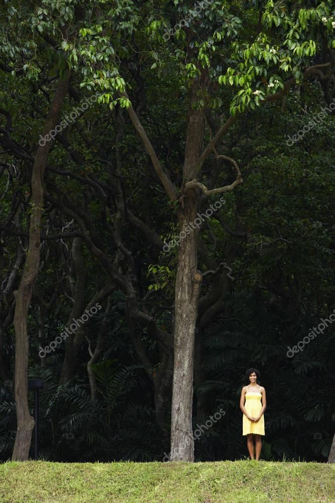 woman in yellow dress standing under trees.