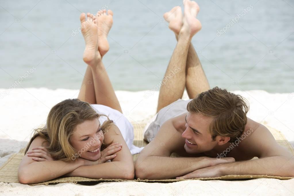couple relaxing on beach mat