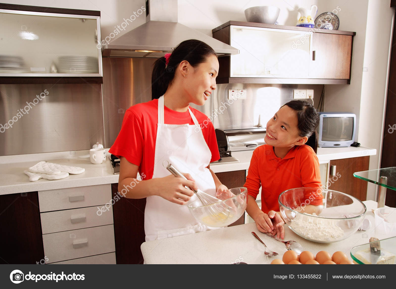Two sisters baking in kitchen — Stock Photo © MicrostockAsia ...