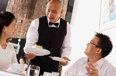 Waiter serving plates of dessert