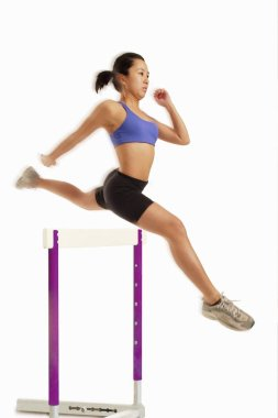 Woman jumping over hurdle