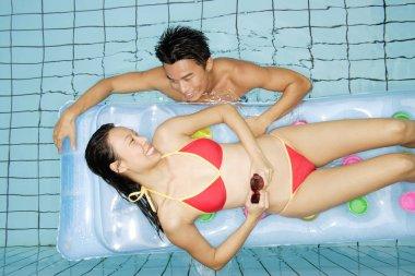 Woman lying on pool raft