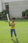 boy holding cricket bat