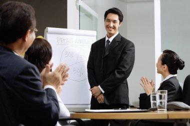 Businessman standing next to flipchart