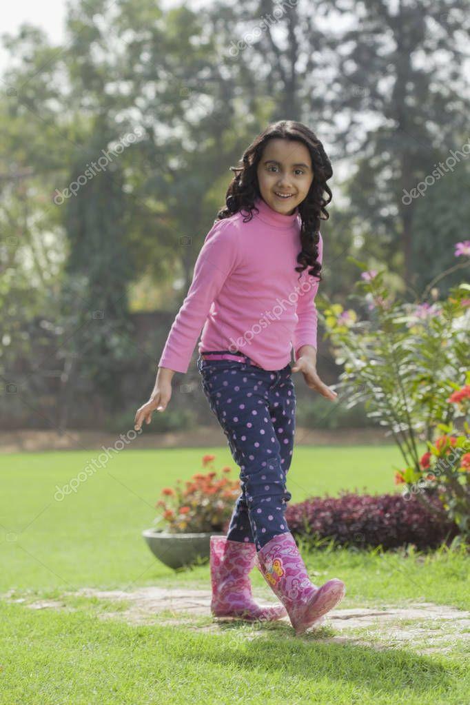Girl in rubber boots dancing in garden