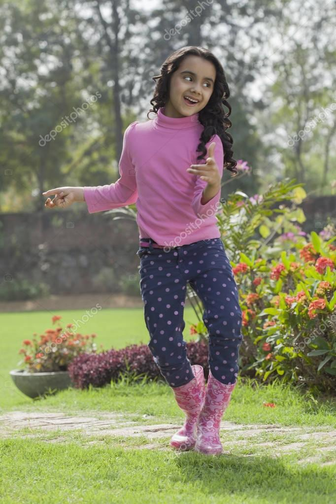 Girl in rubber boots dancing in garden