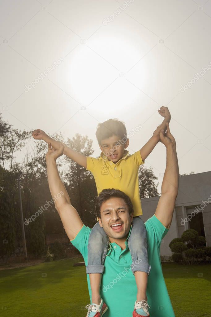 Man holding son on shoulders
