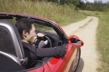 Man driving red convertible sports car