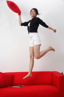 Young woman jumping on sofa