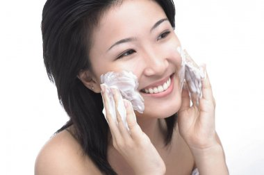 woman lathering soap on her face