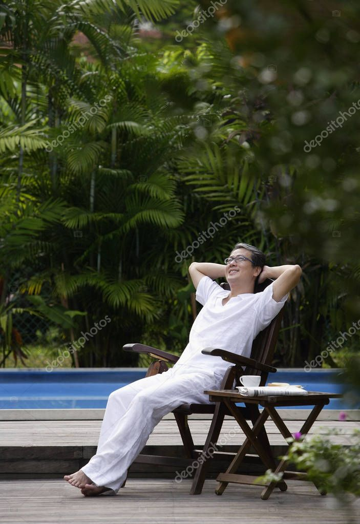 man sitting near swimming pool
