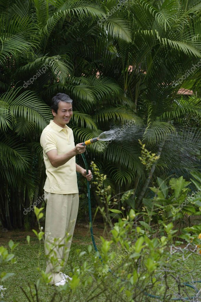 Mature man watering plants