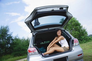 Woman sitting in boot of car