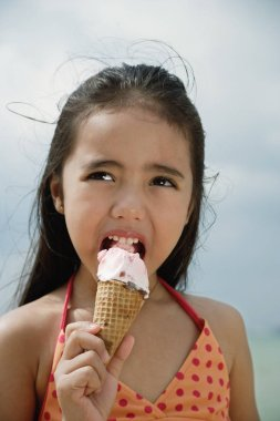 girl on beach eating ice cream