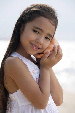 girl holding giant conk shell