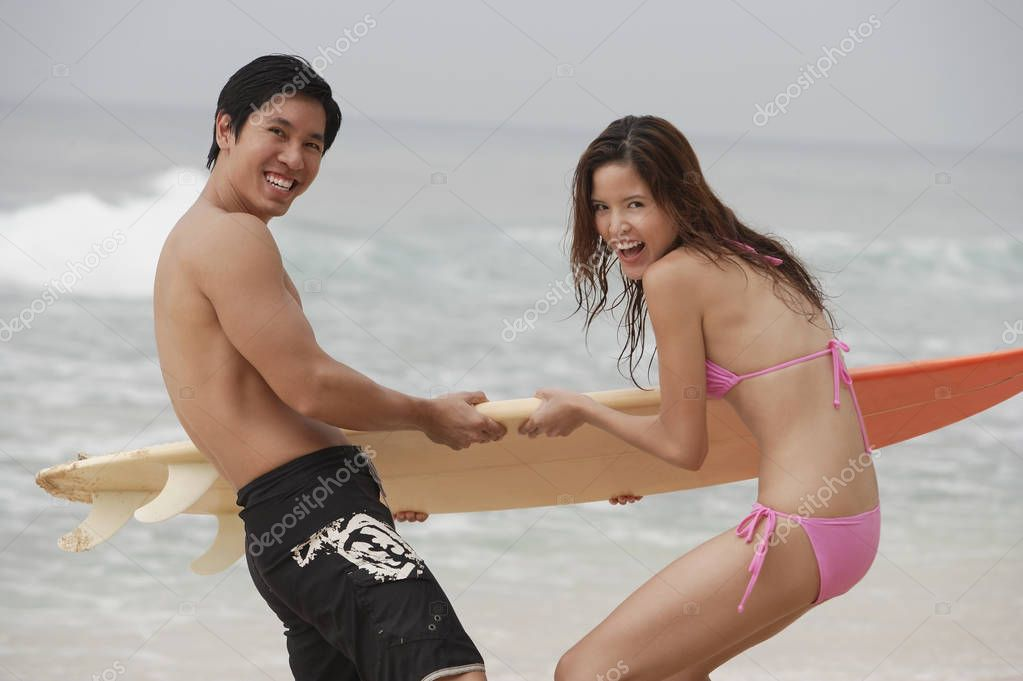 Couple fighting for surfboard