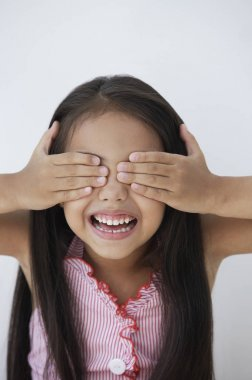 A young girl covers her eyes