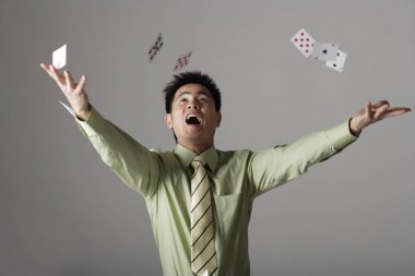 man throwing cards up