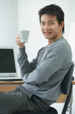 Man with cup relaxing at desk