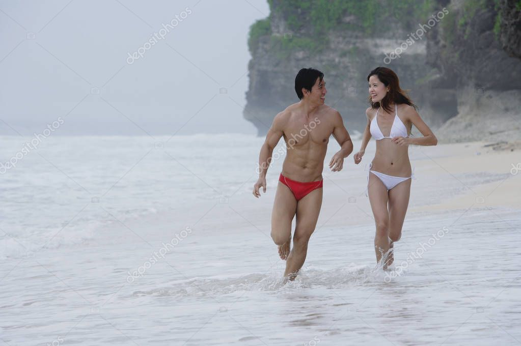 Couple running along beach