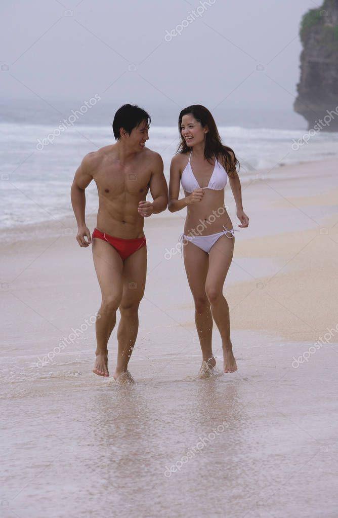 Couple running along beach