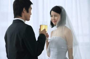 A newlywed couple hold champagne glasses