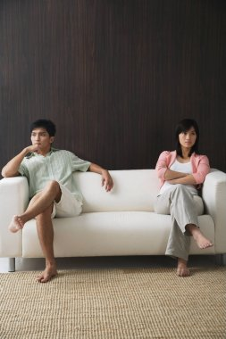 couple sitting on opposite ends of sofa