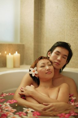 Couple hugging in tub