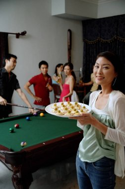 Woman holding tray of appetizers