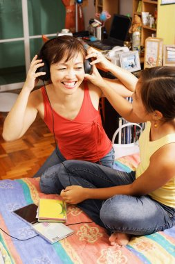 Mother and daughter listening to headphones