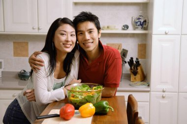 Couple leaning on kitchen counter
