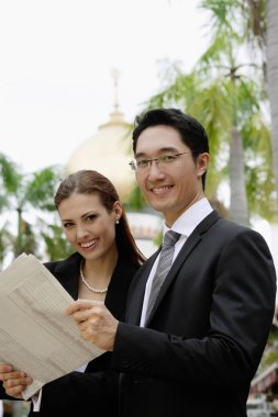 Businessman and businesswoman with newspaper
