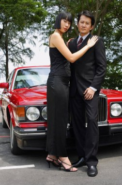 couple standing in front of red car