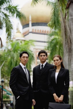 Businessmen and businesswoman in front of mosk