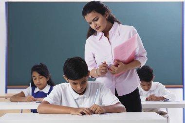 teacher overlooking schoolwork