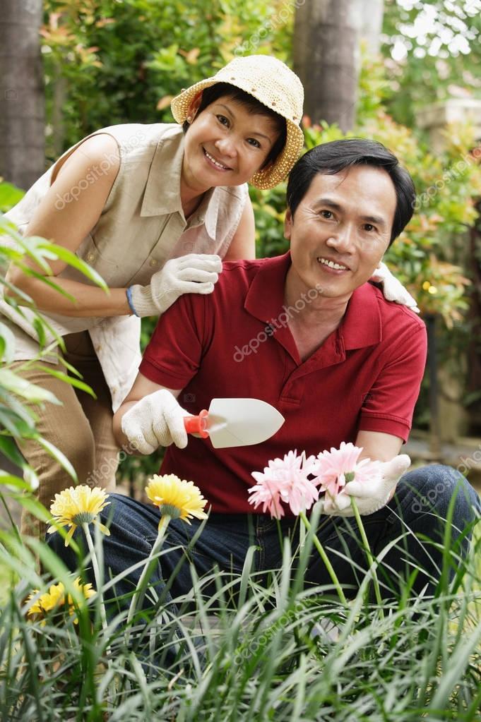 Mature couple smiling at camera while gardening