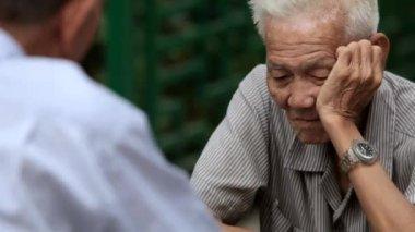 Elderly men playing Chinese Chess