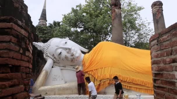 Emberek kiterjedő fekvő Buddha szobor ruhával