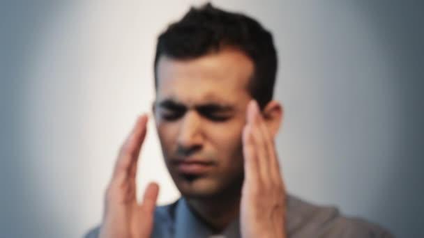 Muž třením chrámy hlavy