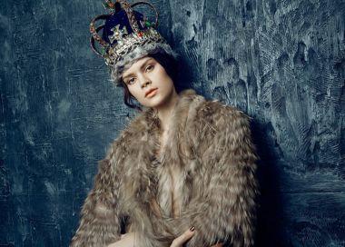 Studio shot of beautiful young woman in crown and fur coat at dark studio background