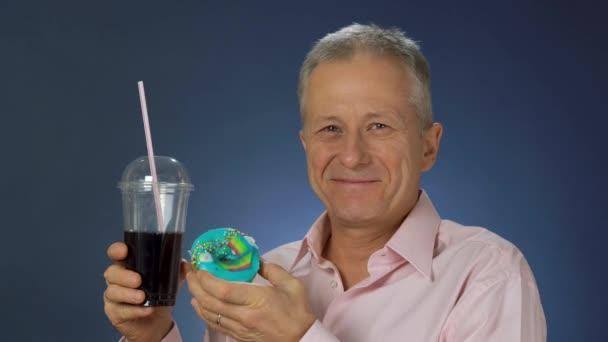 Štíhlý muž středního věku v košili drží sklenici šumivého nápoje a koláč a nabízí, že tento pokrm nahradí šťavnatými hrozny.