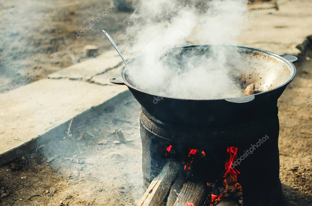 the meat is cooked in a cauldron on the street