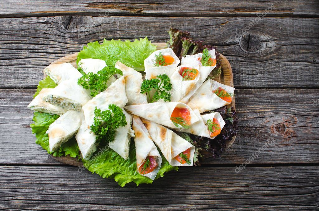On the wooden surface of the rolls, salmon wrapped in pita bread and cheese as a snack