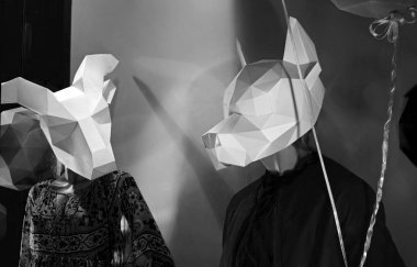 Mannequins with paper masks in the shape of a goat and a wolf. Storefront decoration for Halloween. Two masked mannequins close up.